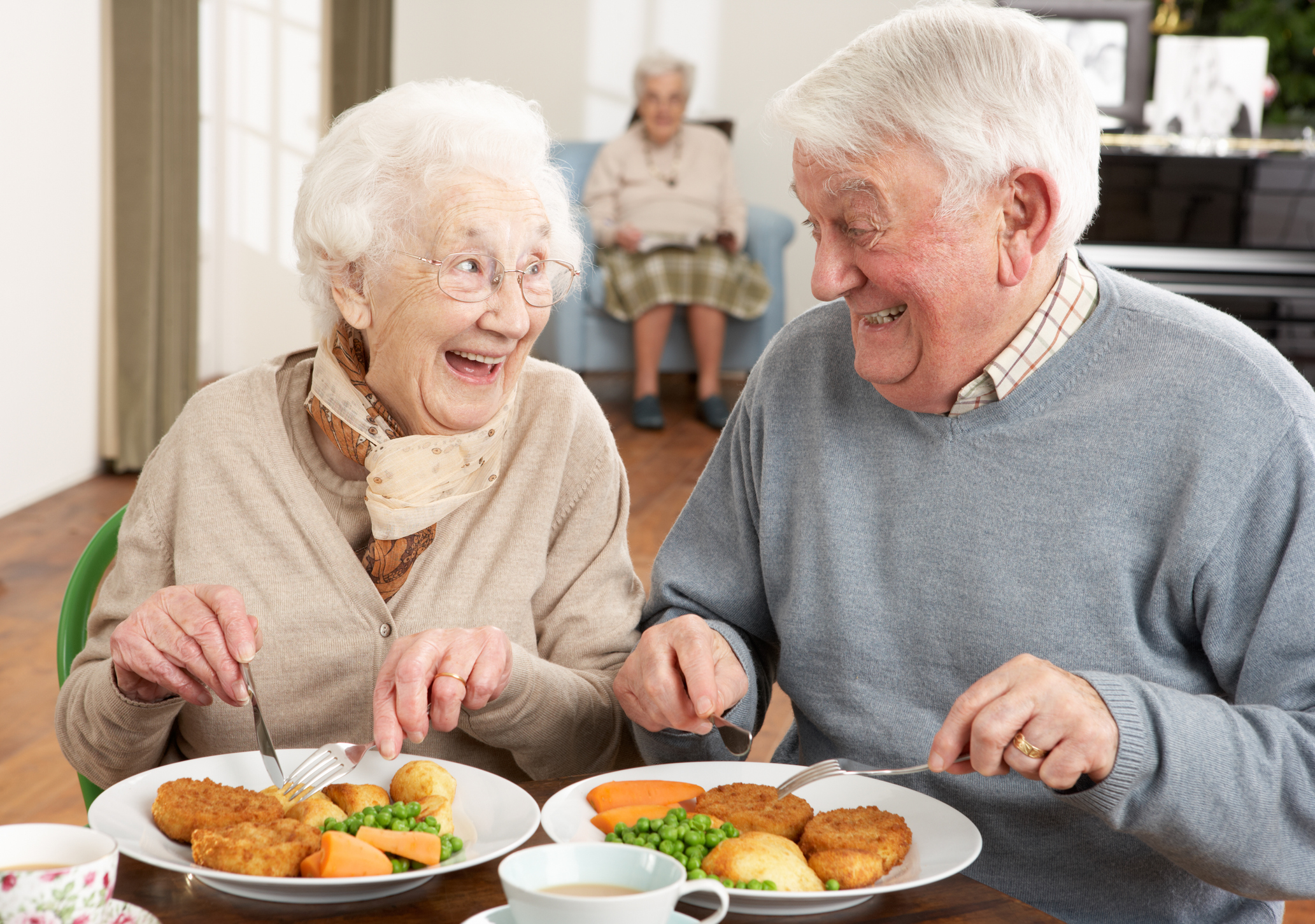 Senior man and woman smile at each other as they hold silverware above plates of food