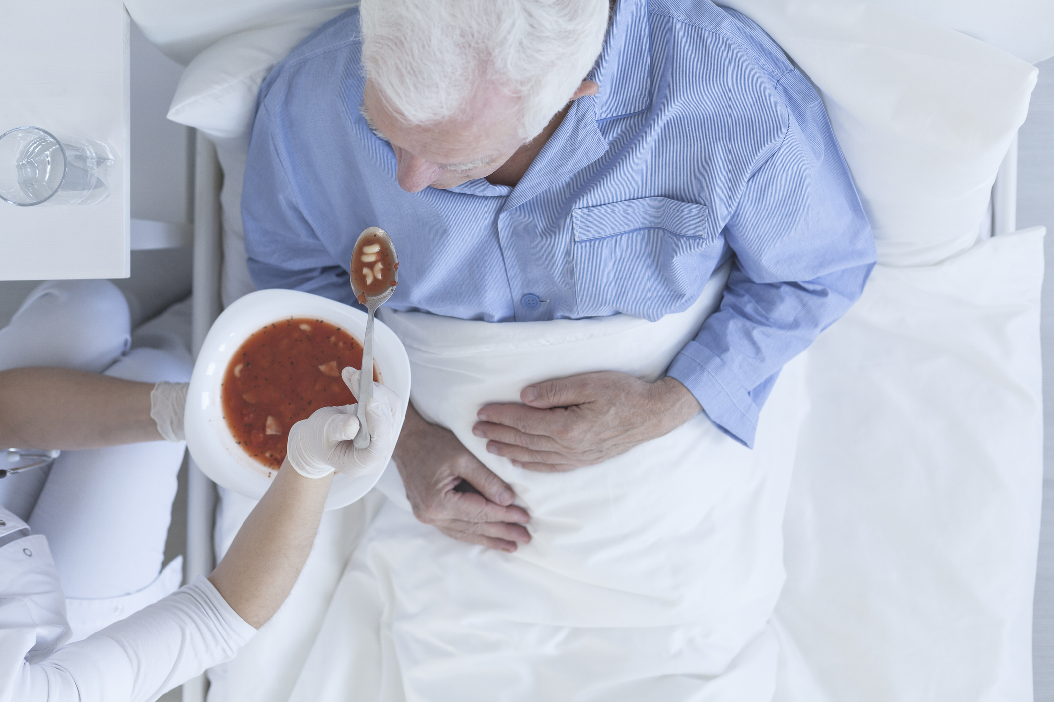 A nursing assistant feeds soup to an older man that is in bed