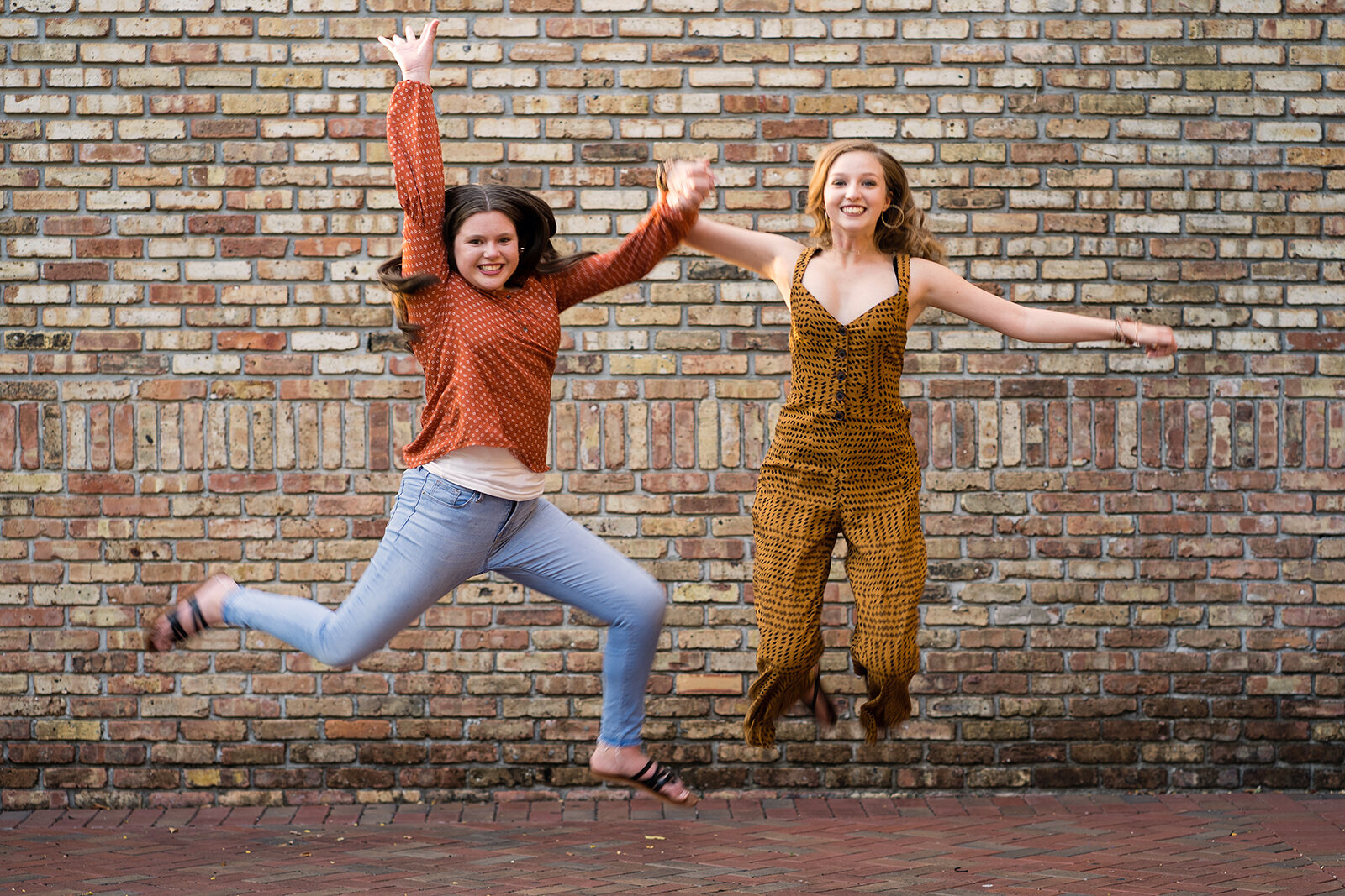 Teen Girls Jump in Front of Brick Wall Plantation Photographer