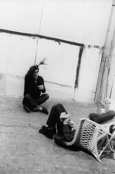 Allen Ginsberg on Floor (gesturing to someone in chair)