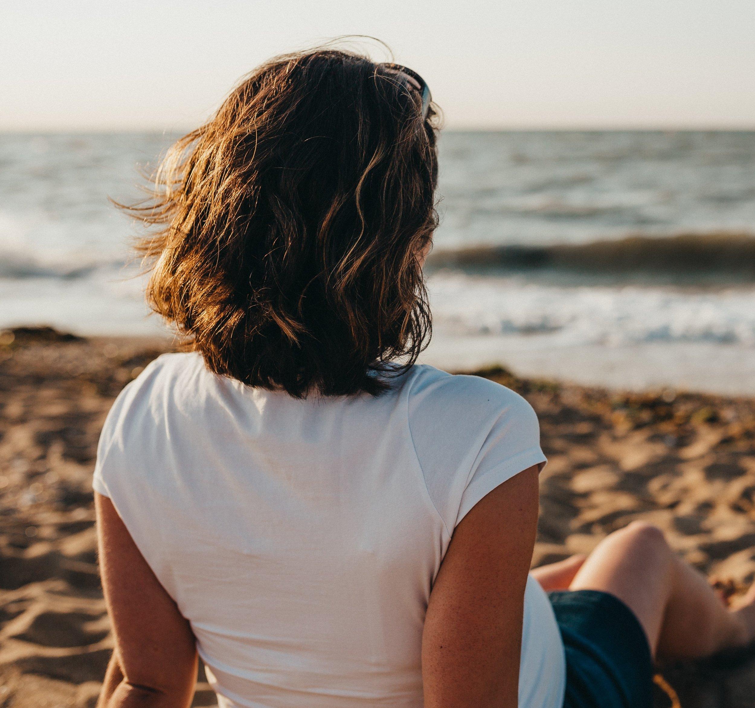 woman sitting on beach watching water xavier-mouton-photographie-2D5sGnLDfYk-unsplash.jpg