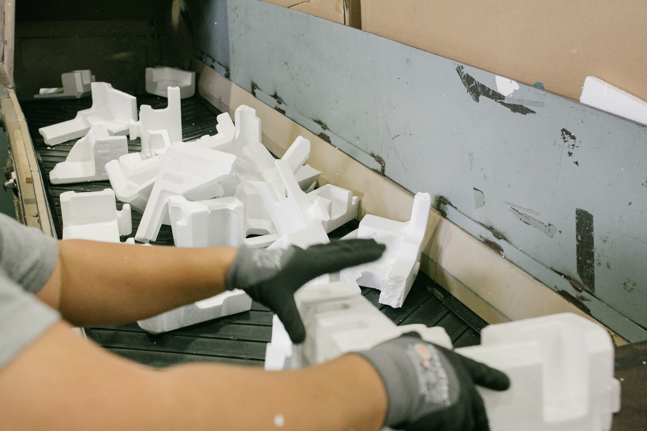 Regenyx employees send discarded polystyrene foam through a machine designed to densify the foam for processing.