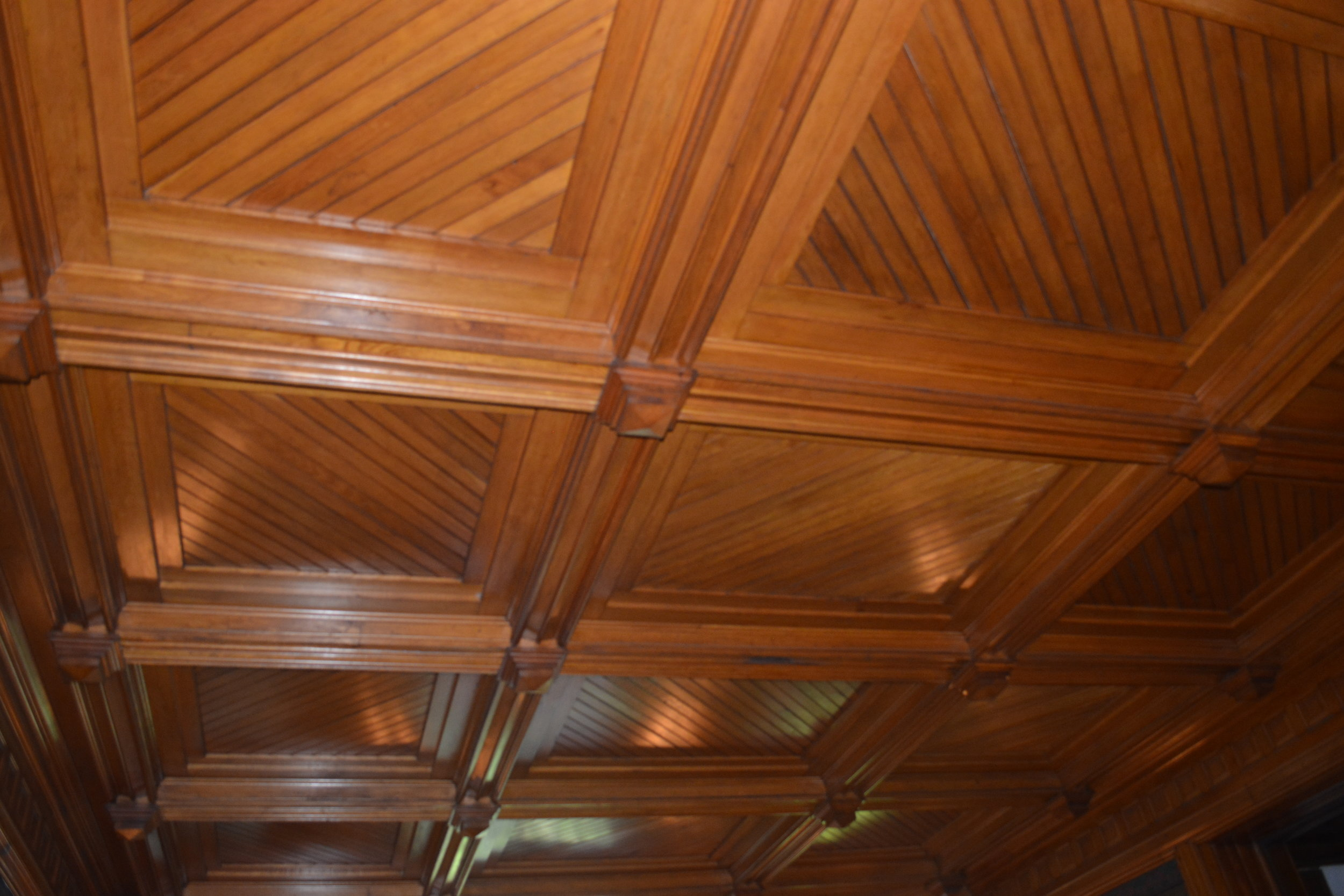 The wood-paneled dining room ceiling