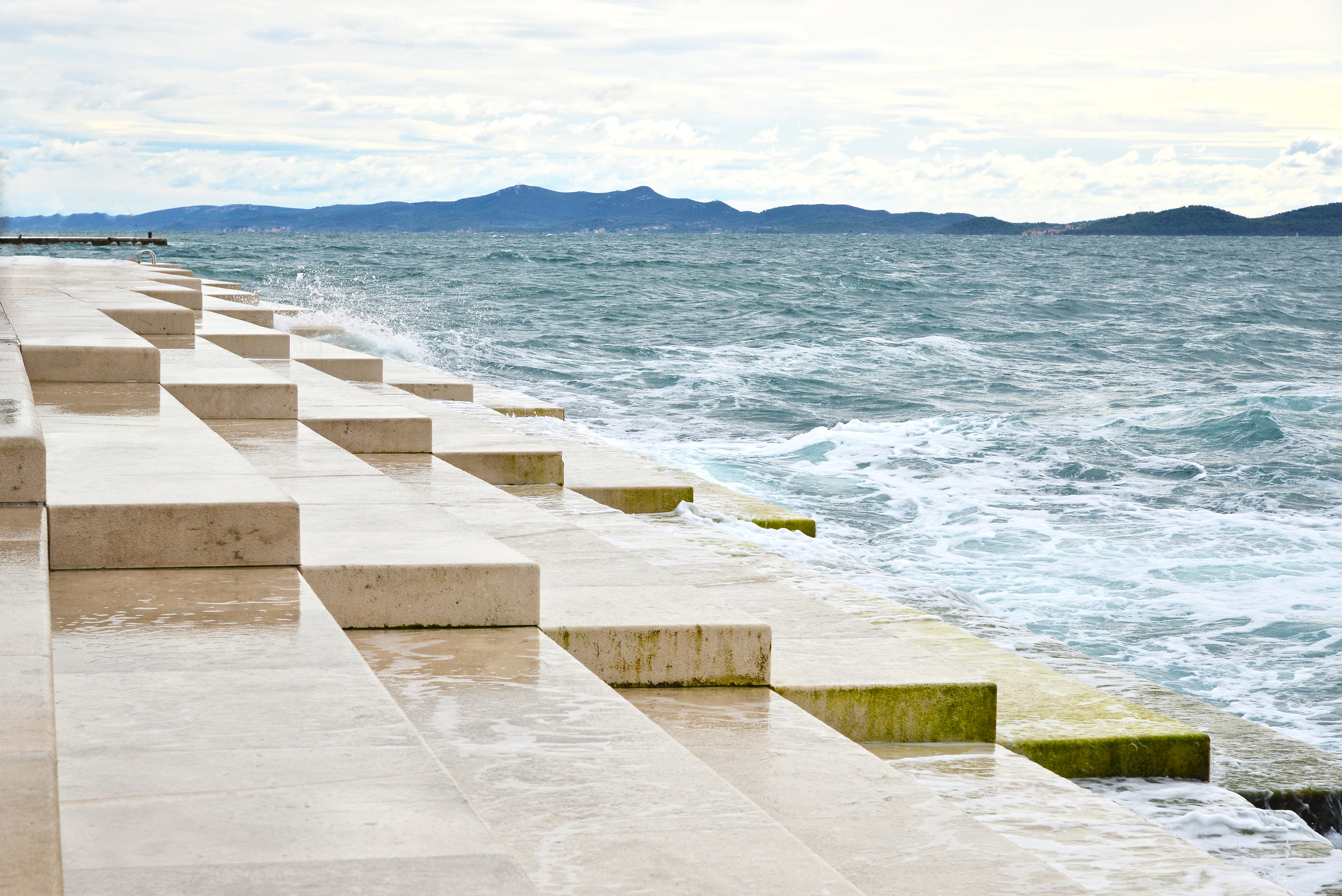 The Sea Sings track#9 - Perched along 230ft.of coastline in Zadar, Croatia, lays an architectural wonder: a series of marble steps that join the land into the sea. These steps conceal a labyrinth of tubes that produce harmonic tones as the sea water rushes in. Mesmerized by the haunting music the wind and tides were composing, I sat down at my piano, turned on the recorder, and improvised an accompaniment. This was done in one take, and I have only ever played this song once. Special thanks to Tom Eaton for mixing The Sea Organ with my song, THE SEA SINGS.