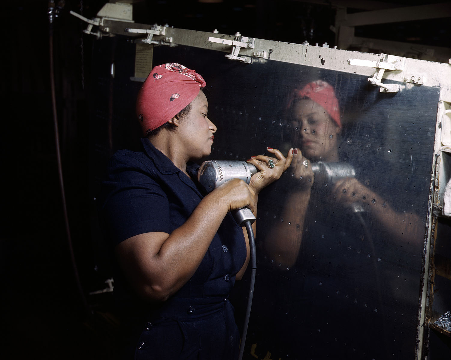 "A real-life ""Rosie the Riveter"" operating a hand drill at Vultee-Nashville, Tennessee, working on an A-31 Vengeance dive bomber. Circa 1943."