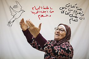 """Layla Al Hussein imagines a world of peace as part of Mark Strandquist and Courtney Bowles' """"Where the Lines of Our Hands Meet"""" workshops. English translation: """"These are my words and my poetry, and I hope they reach the people: I release the doves of love and peace."""""""
