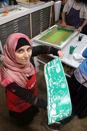 "Asmaa Diab shows the silkscreen accordion book she made in Erik Ruin's ""Journeys"" workshops.  Photo credit: Hussam Al-Obaidi."