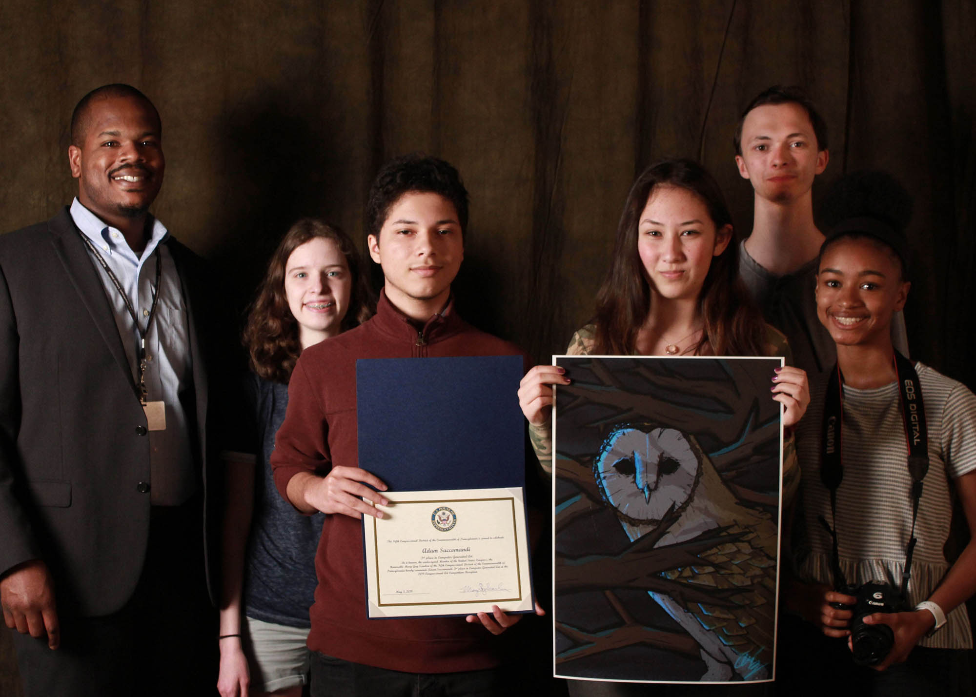 Award-winning Strath Haven artists at the Congressional Art Competition Show joined (left to right) SHHS Principal Dr. Kris Brown; Adie Woolf: 3rd Place for Printmaking; Adam Saccomandi: 3rd Place for Computer Generated Art; Maria Hess: 2nd Place for Black & White Drawing; Will Garrett: First Place for Photography; and Maysie Lewis: 3rd Place for Photography. Absent but represented by his work was Ari Burch: 1st Place for Computer Generated Art.  Photo by Kate Plows.