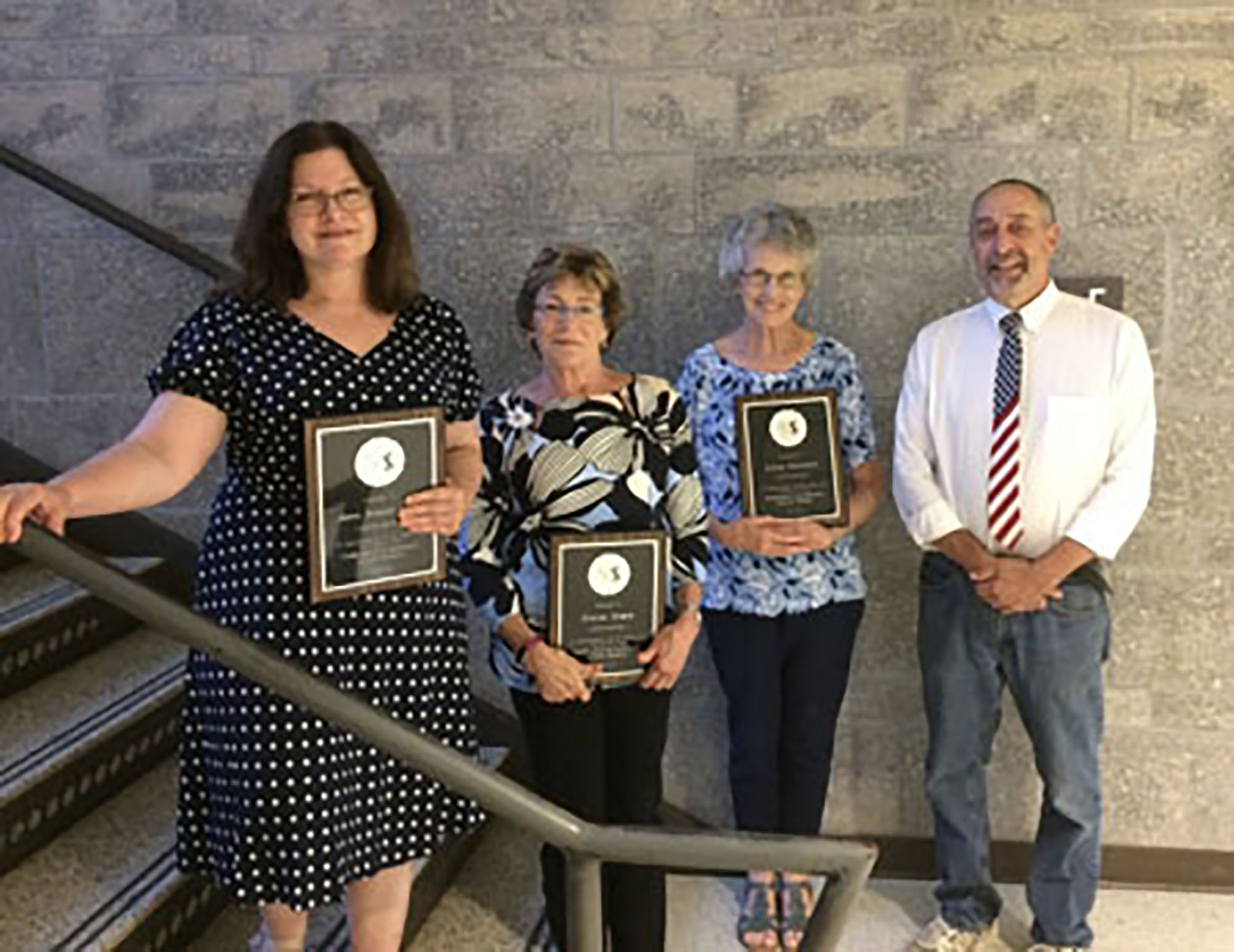 Four of the 12 teachers who are retiring this year from the Wallingford-Swarthmore School District attended Monday's School Board meeting and received honorary plaques. From left to right: Jane Rondepierre, Diane Silzle, Anne Mulhern, and Mark Rosenberg.  Photo by Philip Host.