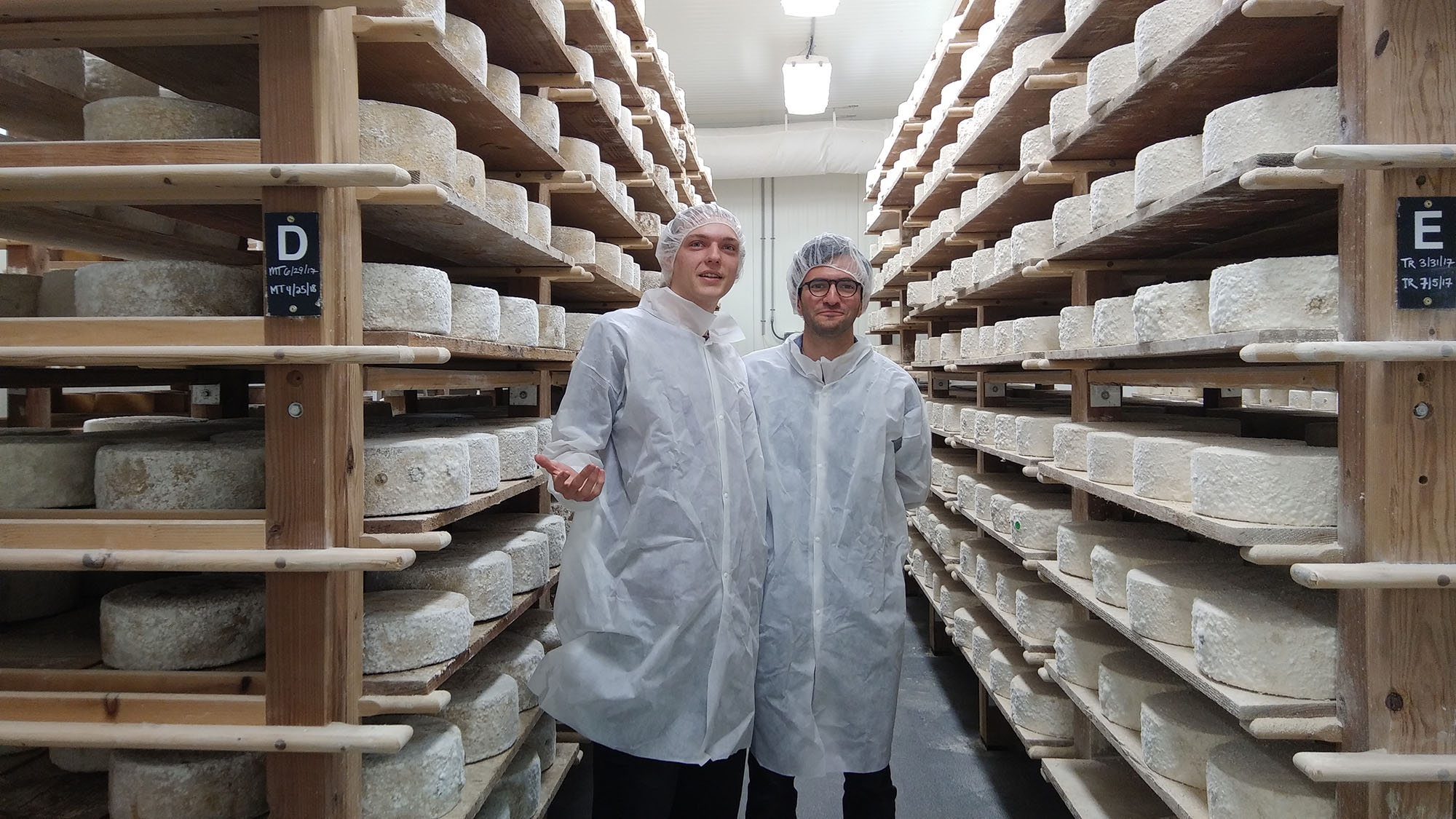 Malcolm Reynolds (left) and Alex Schaff among the wheels of aging cheeses in Arethusa Farm Dairy's cellars.