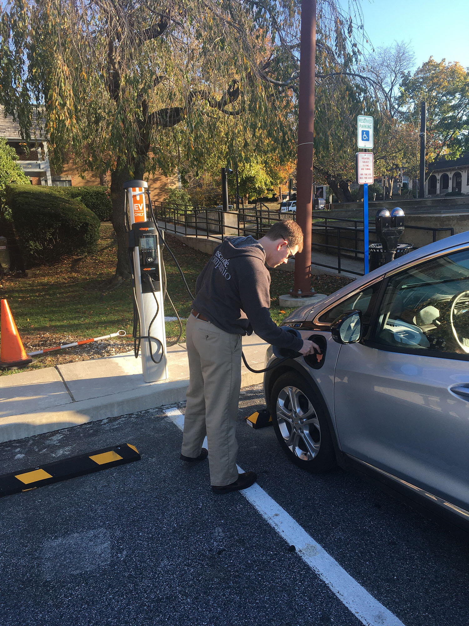 Michael Raffaele plugs in his Chevy Bolt at Swarthmore's new electric vehicle (EV) charging station in Central Park, adjacent to Borough Hall.  Photo by Kathleen Raffaele.