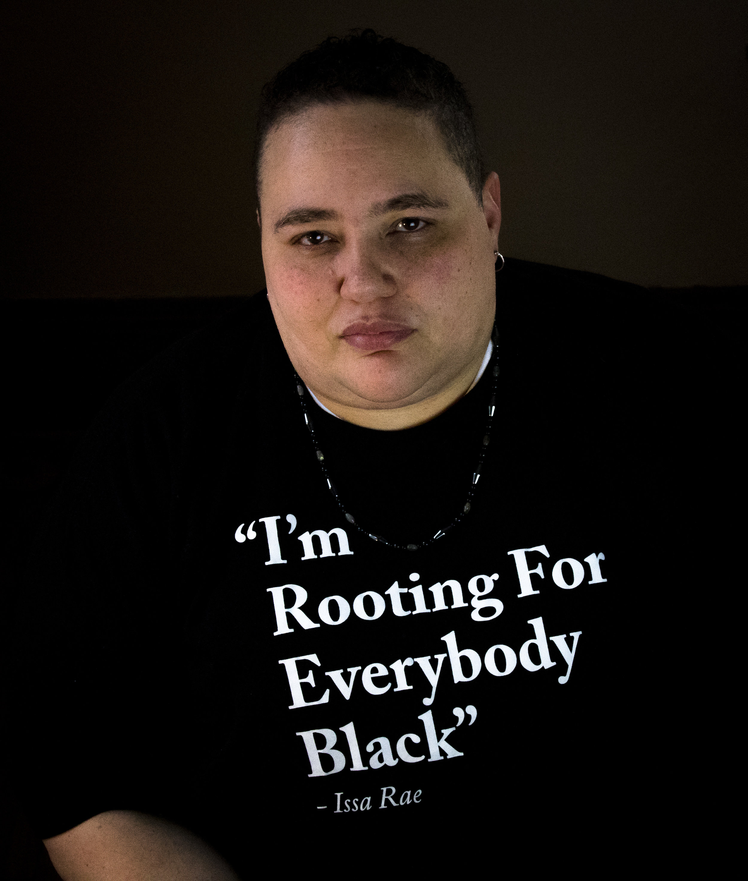 "Image description: Stephanie looking intently at the camera wearing a shirt with text, ""I'm rooting for everybody black. -Issa Rae"""