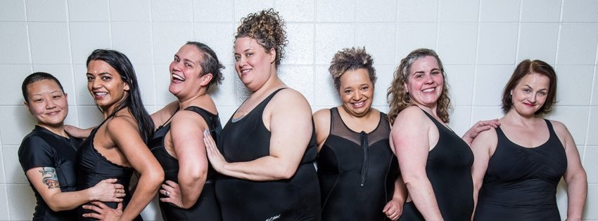 Image description: Group photo of the Subversive Sirens, standing in a row in black swim suits.