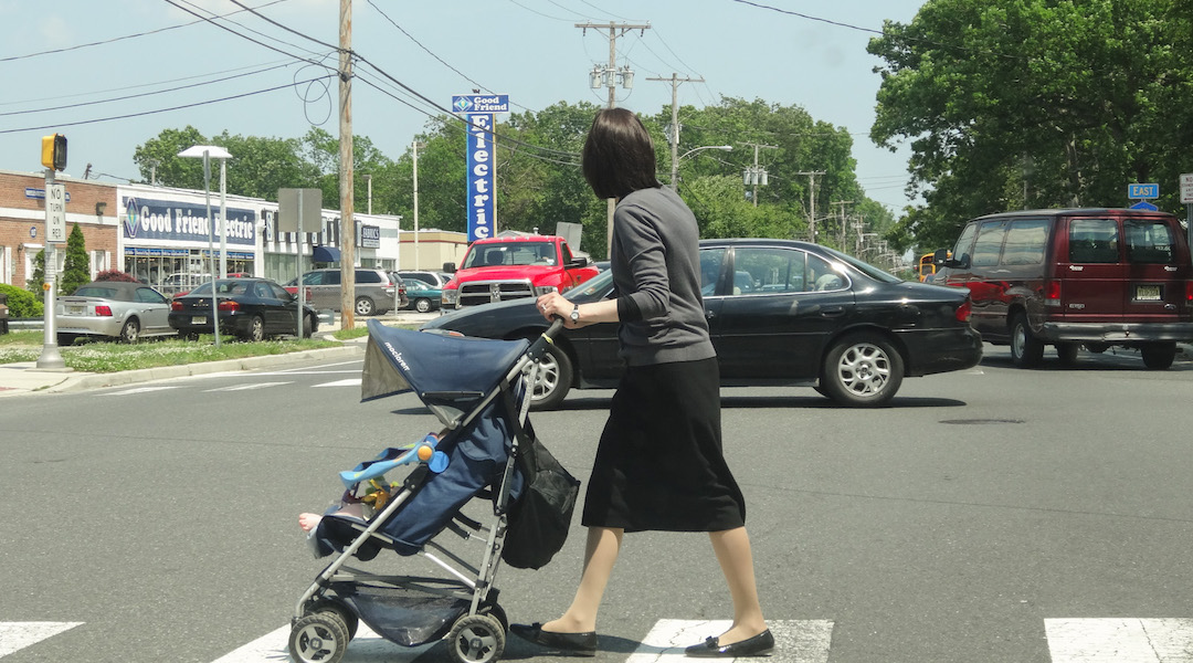 An Orthodox woman pushes a stroller in Lakewood, N.J. in 2013. The population in the largely haredi Orthodox town has boomed in the past couple of decades, and haredi families are looking to move to neighboring towns. (Dennis Fraevich/Flickr)