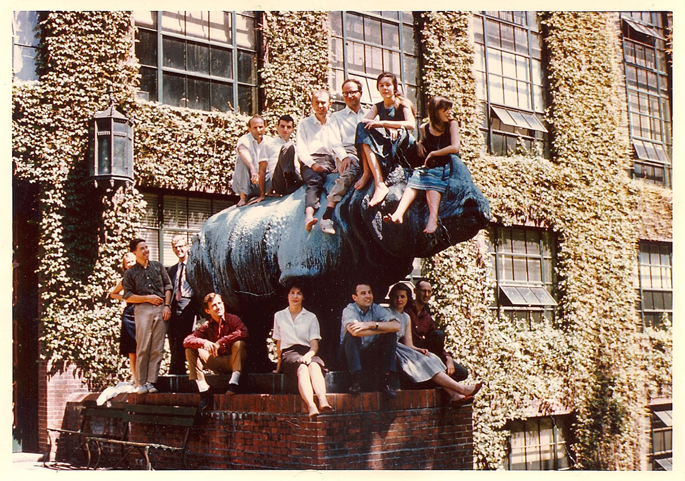 Summer lab techie Barbara Riddle (second from right, on top of rhinoceros) shares a perch with  James Watson  (third from the left, barefoot) and his research group in front of the Harvard biology labs in 1962.