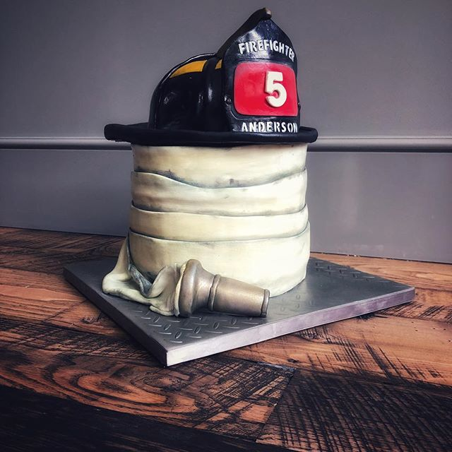 Firefighter cake with custom name badge. The helmet, hose and even the board finish are all edible!
