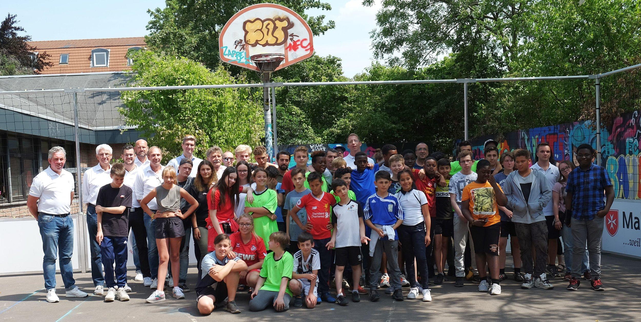 """Die Repräsentanten der """"Kölsche Fründe"""" auf dem mobilen Street Soccer Court mit den jungen Kickern und Vertretern der OT Lucky's Haus und des SKM in Köln-Bilderstöckchen."""