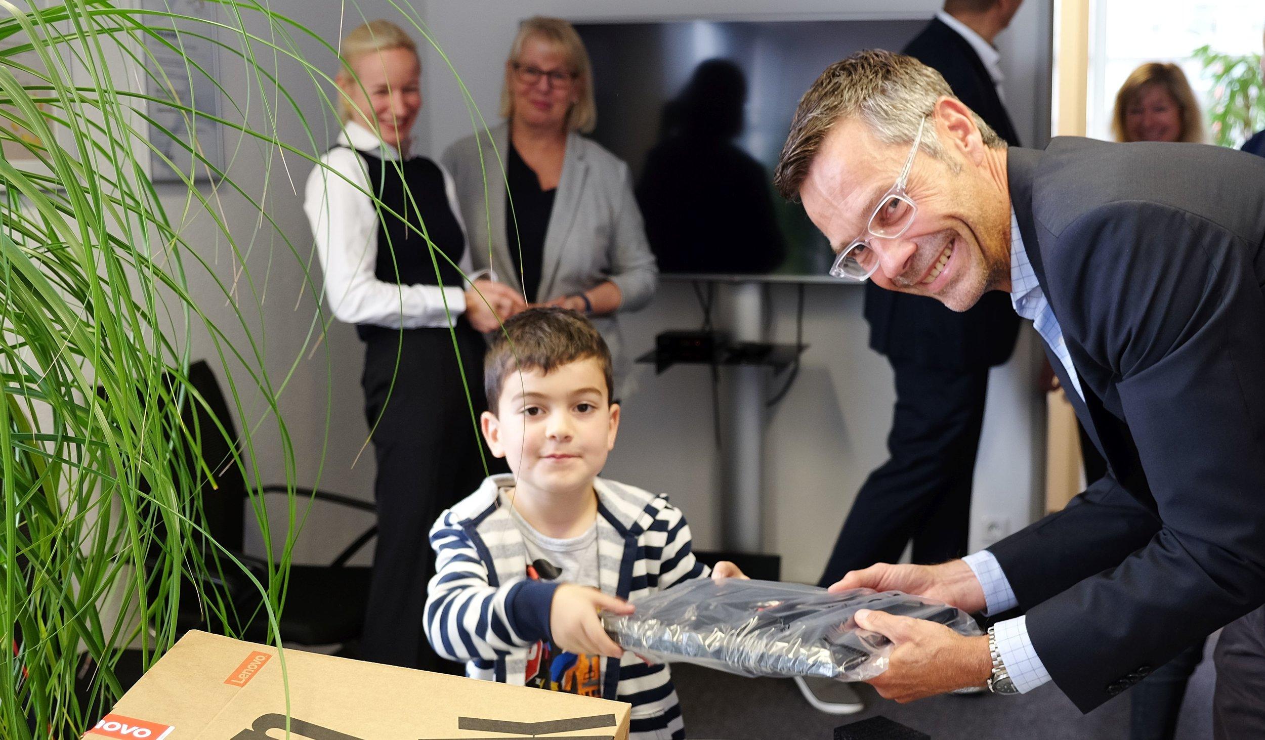 Der 7-jährige Ismail lässt sich von Sven Sommer die Laptops zeigen. Foto: Malteser