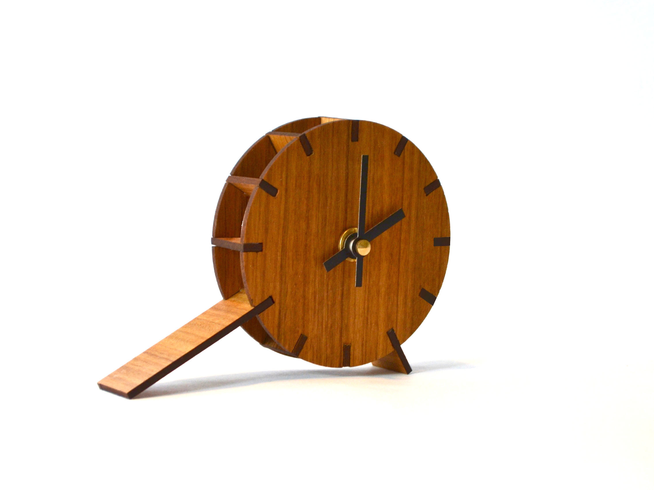 - The Table-Tock Clock has been created from an ethos of simple, functional design that carries with it a sense of character. The Table-Tock Clock achieves this by merging the structure, function and aesthetics into one.Made from laser cut walnut timber.