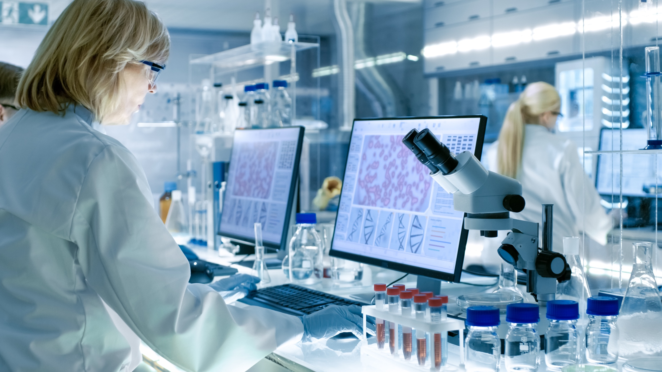 Senior-Female-Scientist-Works-with-High-Tech-Equipment-in-a-Modern-Laboratory.-Her-Colleagues-are-Working-Beside-Her.-949947192_2313x1301.jpg