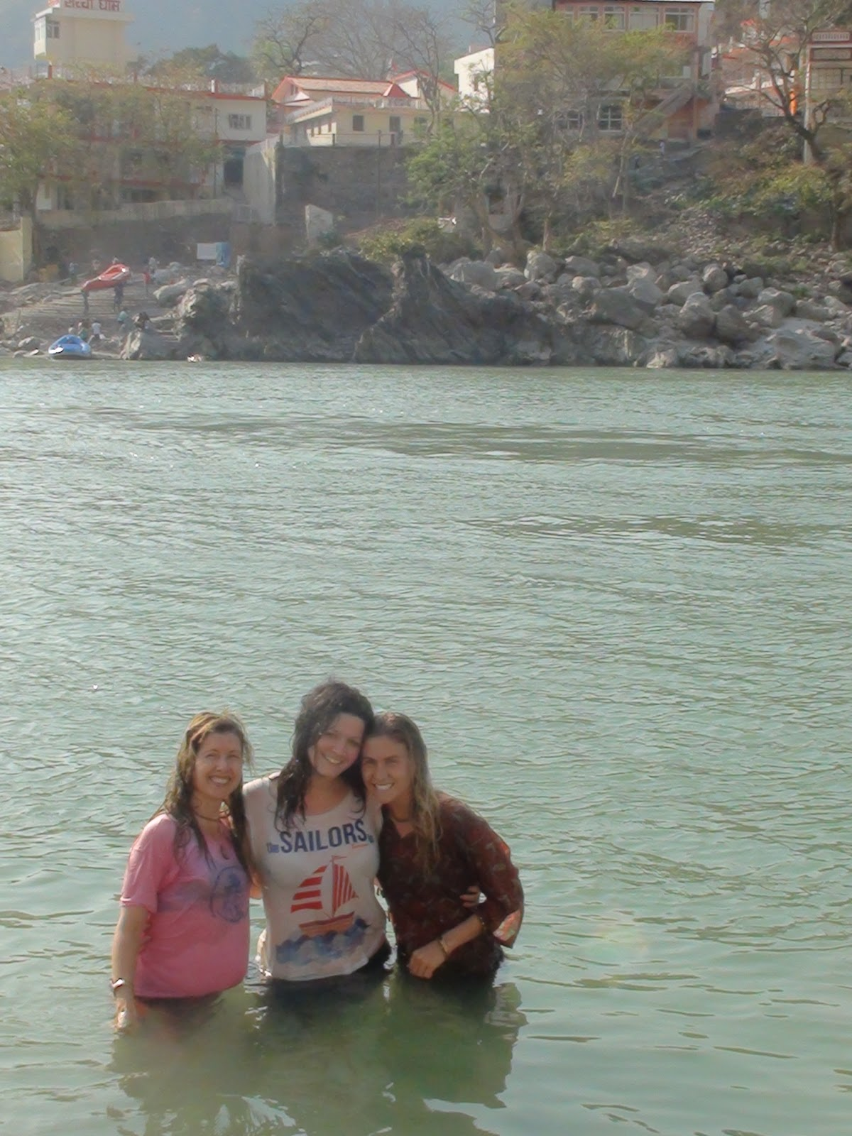 Three women, dunking in the River Ganges to cleanse ourselves of our sins