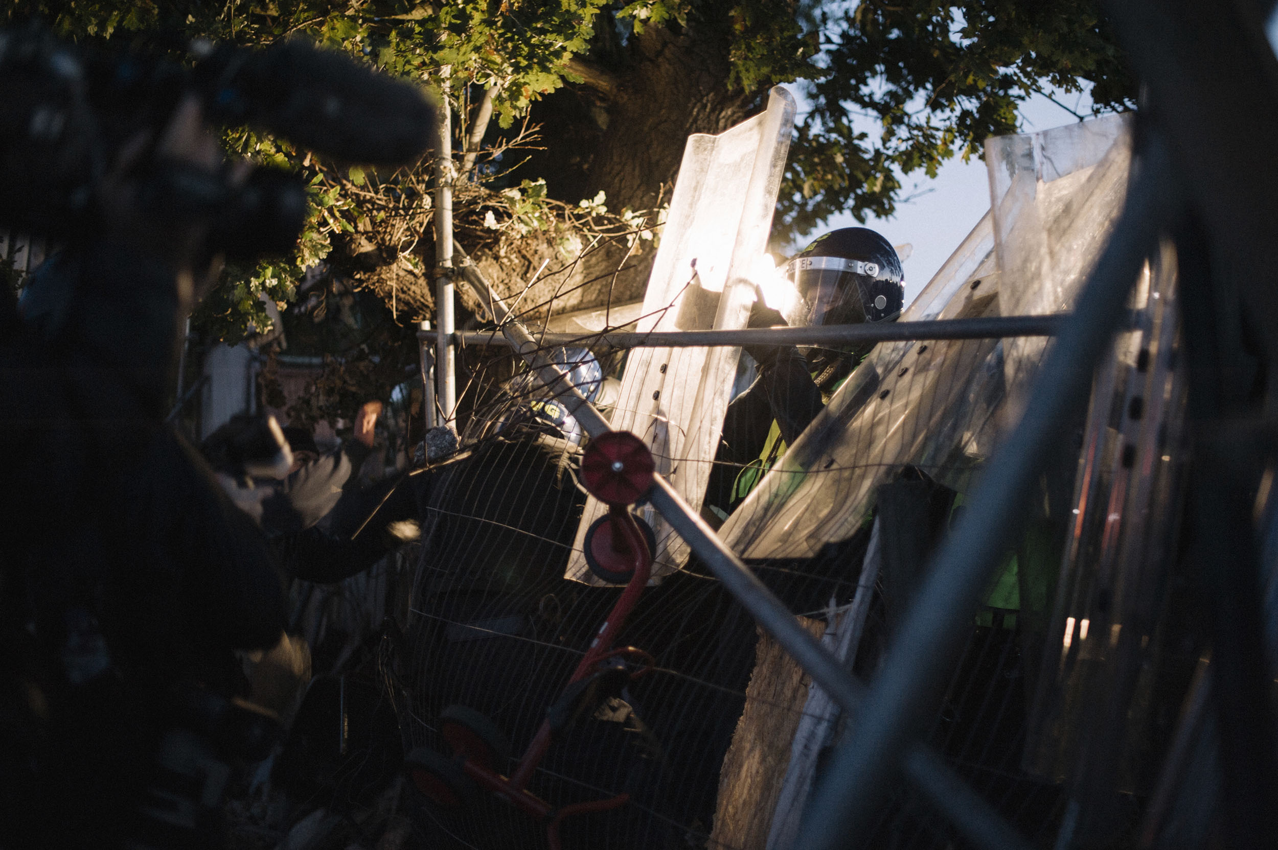 Police breach Dale Farm's perimeter, using tasers to neutralize and push back activists who reinforce barriers.