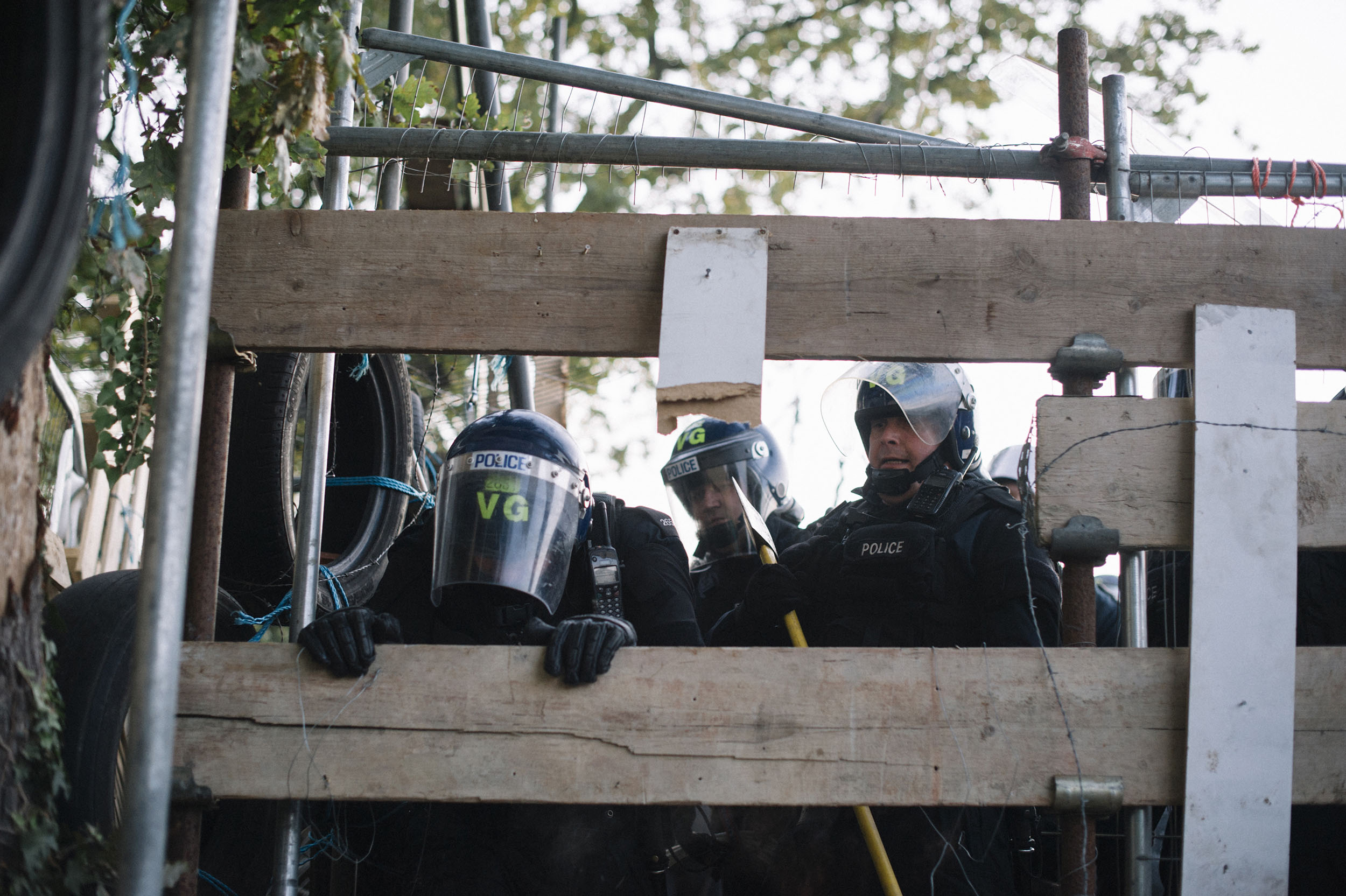 Police use axes to break the barriers of the activists, slowly they gain control of the site.