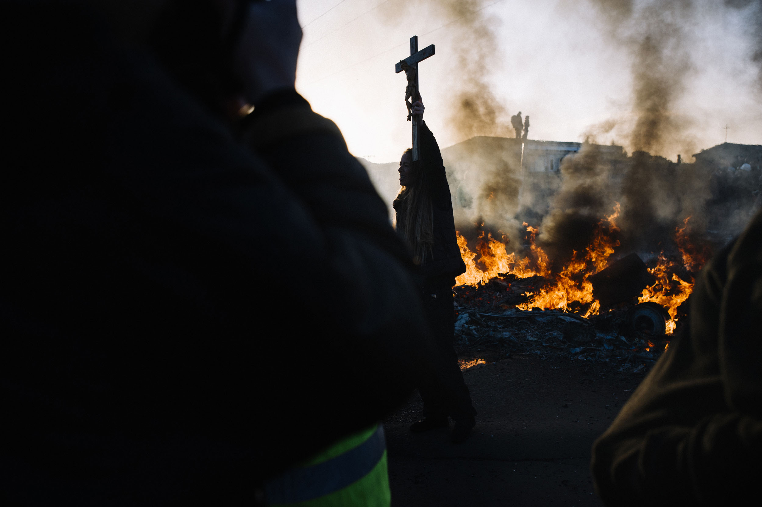 Activists and Gypsies hold crucifixes in the air, as caravans burn.