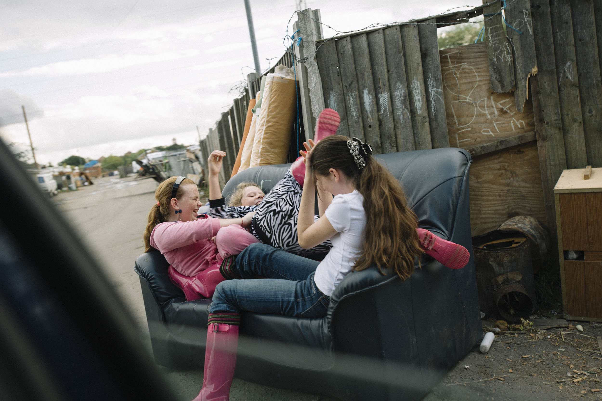 Younger residents play fight on an old sofa near the main gates to Dale Farm.