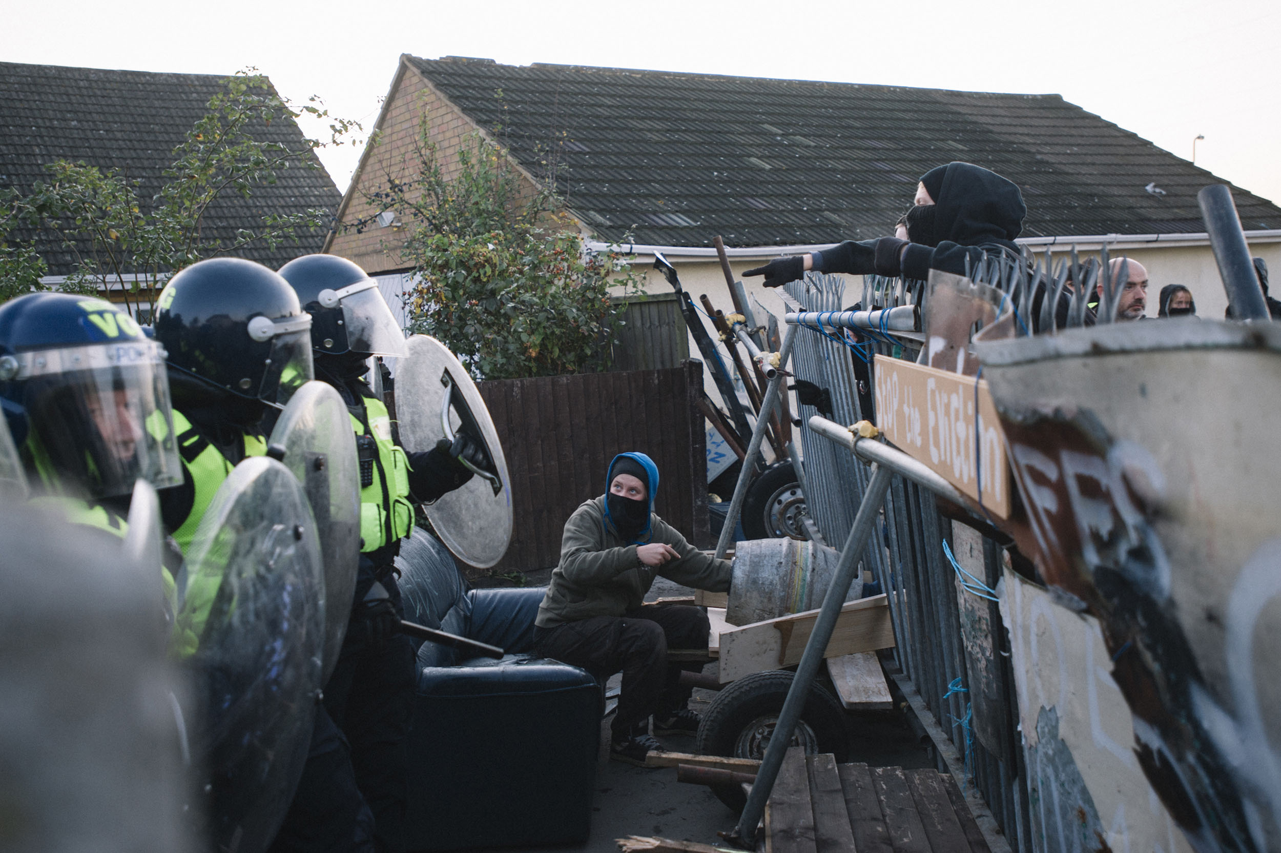 An activist locks her arm inside a concrete filled barrel, as a barrier against police.
