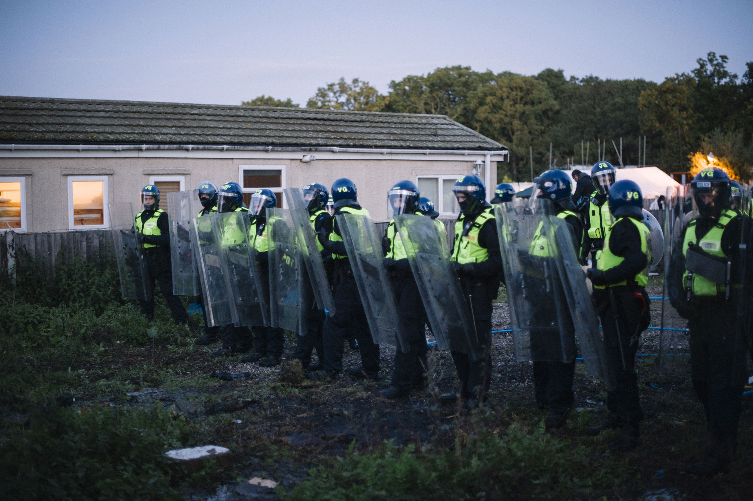 Police congregate inside Dale Farm, forming protective barriers behind their shields.