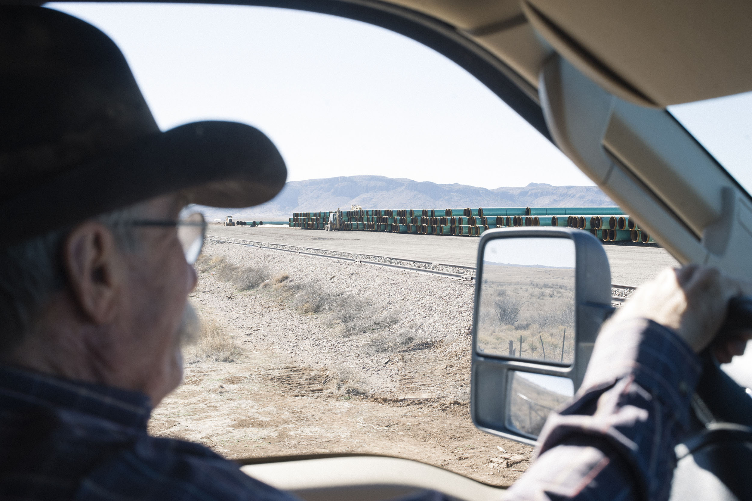 Joel Nelson drives past a pipe storage yard on ranch land adjacent to his.