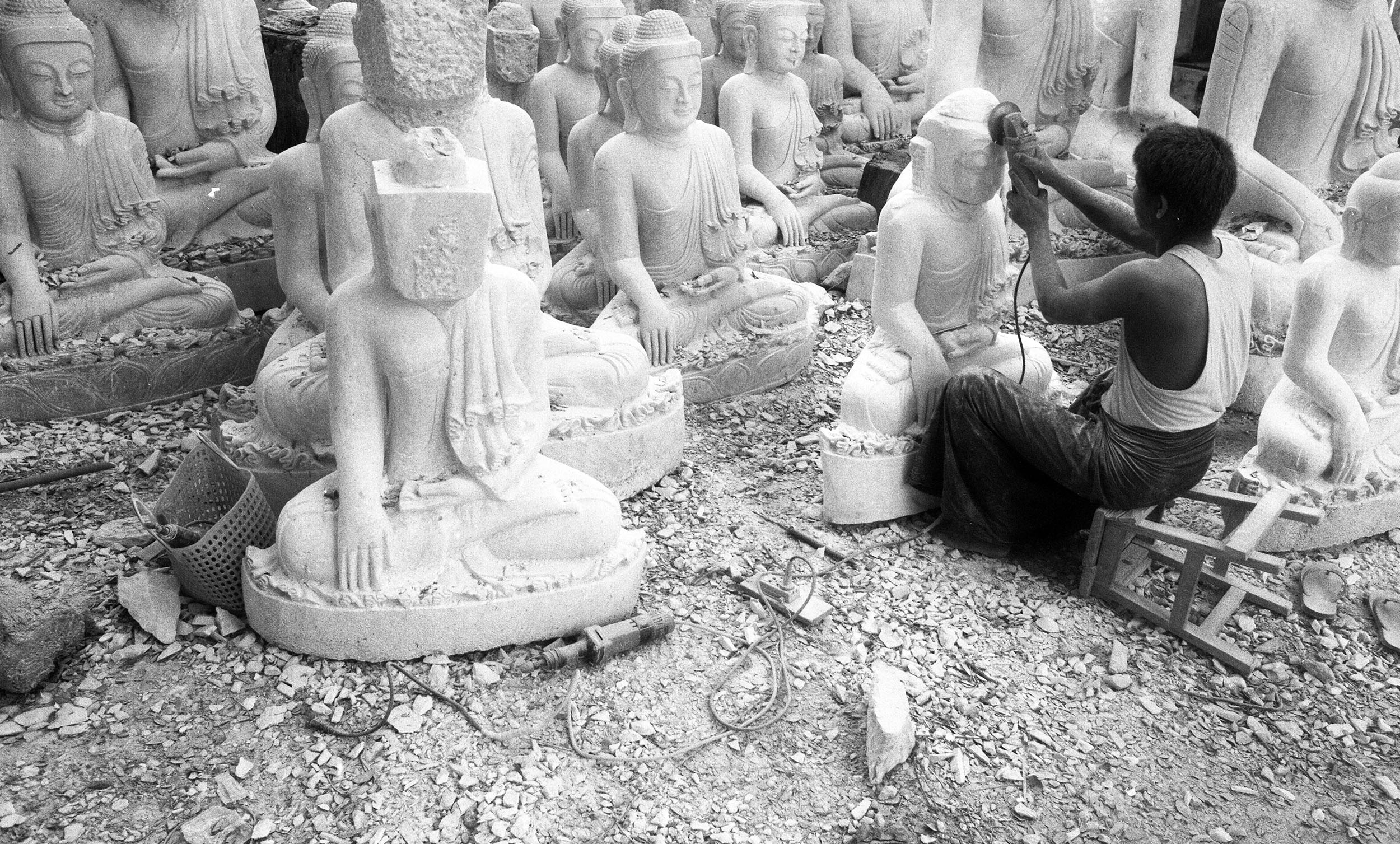 A sculptor puts the finishing touches to Buddha's face in Mandalay.