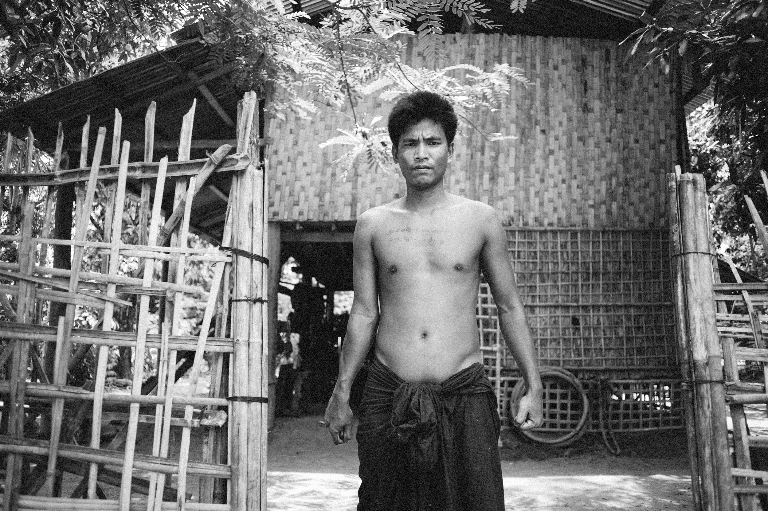 Guang Chwang, 34, stands guard outside his family's home on Sittwe's front line of fighting.