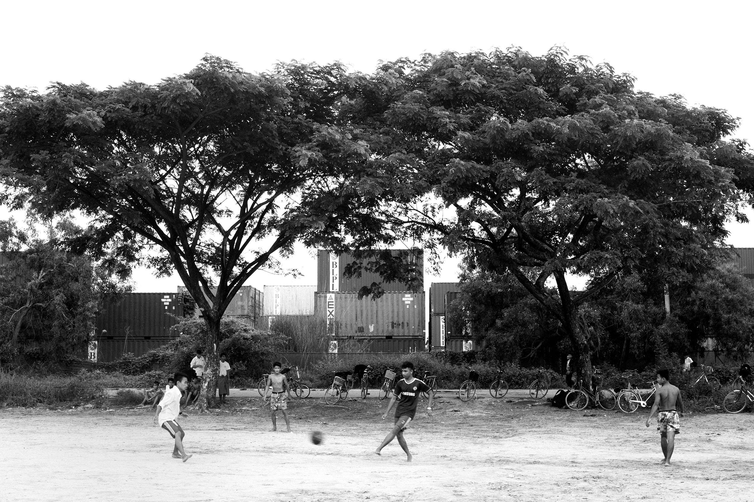 Boys play football in Hlaing Thayar.