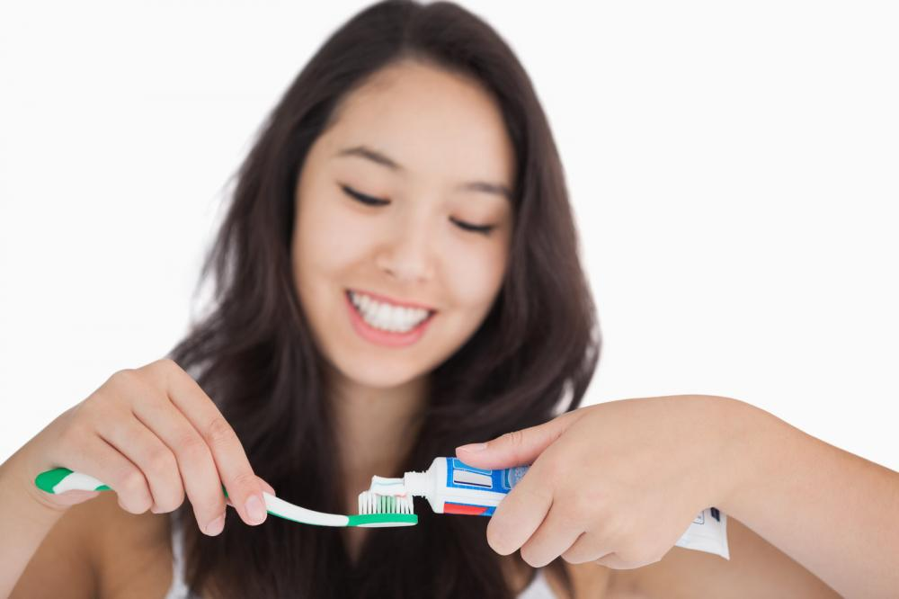 woman-putting-toothpaste-on-toothbrush.jpg