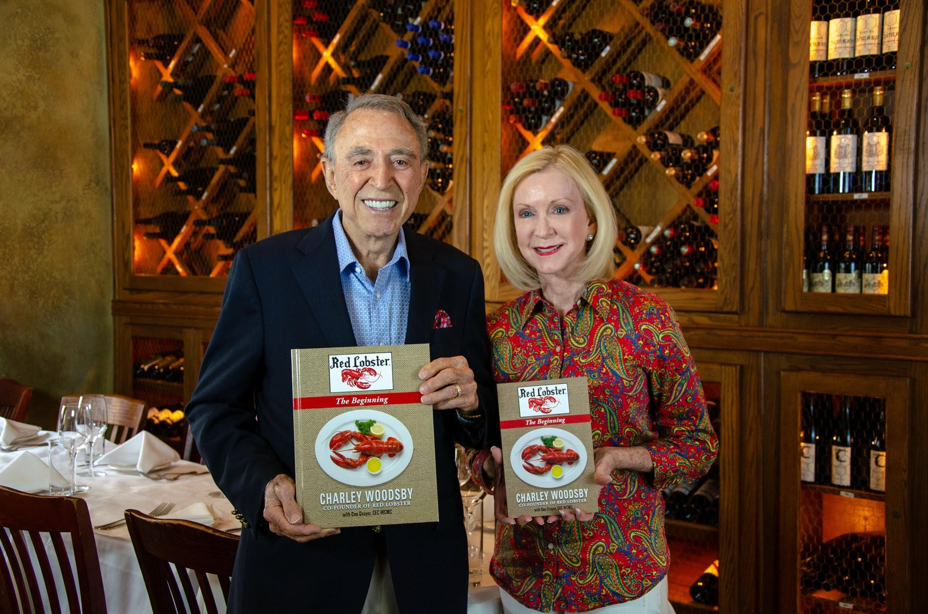 Charley and MaryLou Woodsby with 50 year pictorial history of Red Lobster