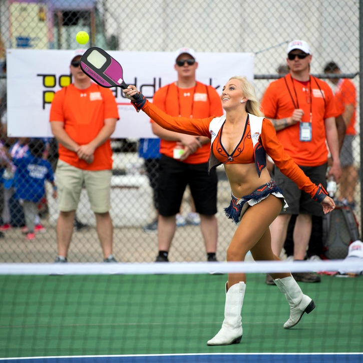 Play it with your boots on!   Denver Broncos Cheerleader McKenna Hester plays pickleball during an exhibition day for families during the 2018 DoD Warrior Games at the Air Force Academy in Colorado Springs, Colo. June 4, 2018. DoD photo by EJ Hersom