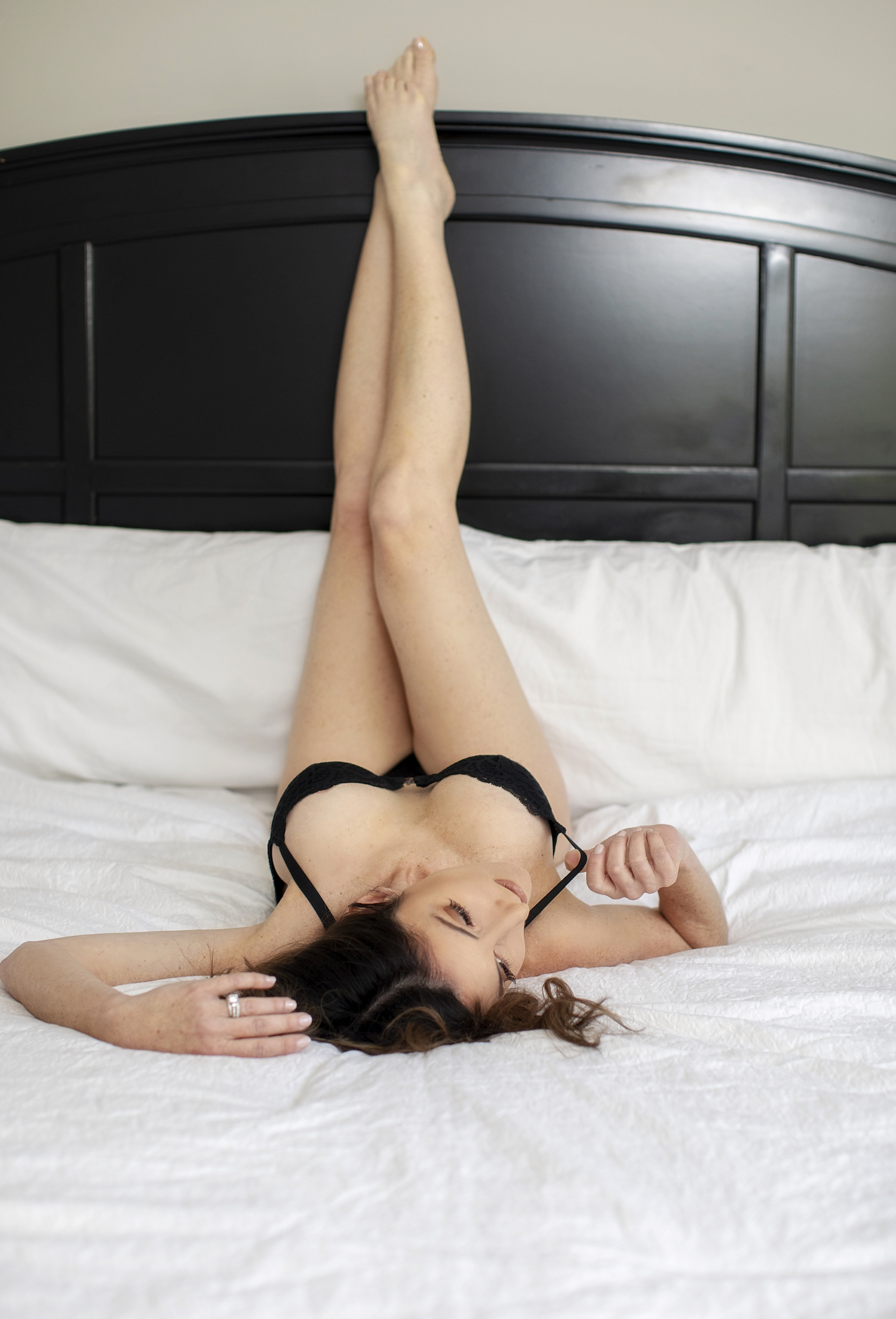 Sexy boudoir photo of a woman in black lingerie while lying on a bed.
