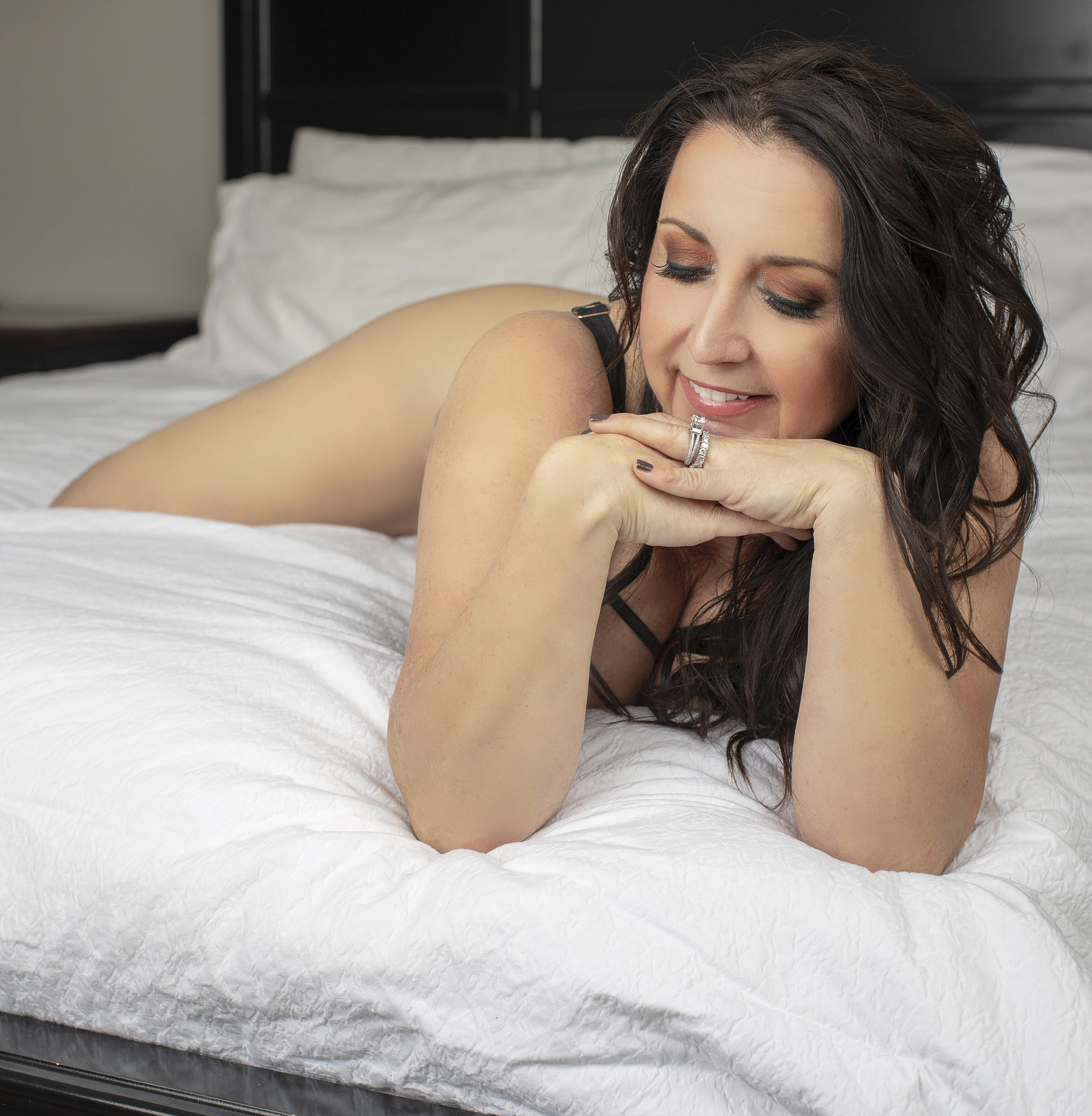 Boudoir style photograph of a smiling woman in black lingerie.