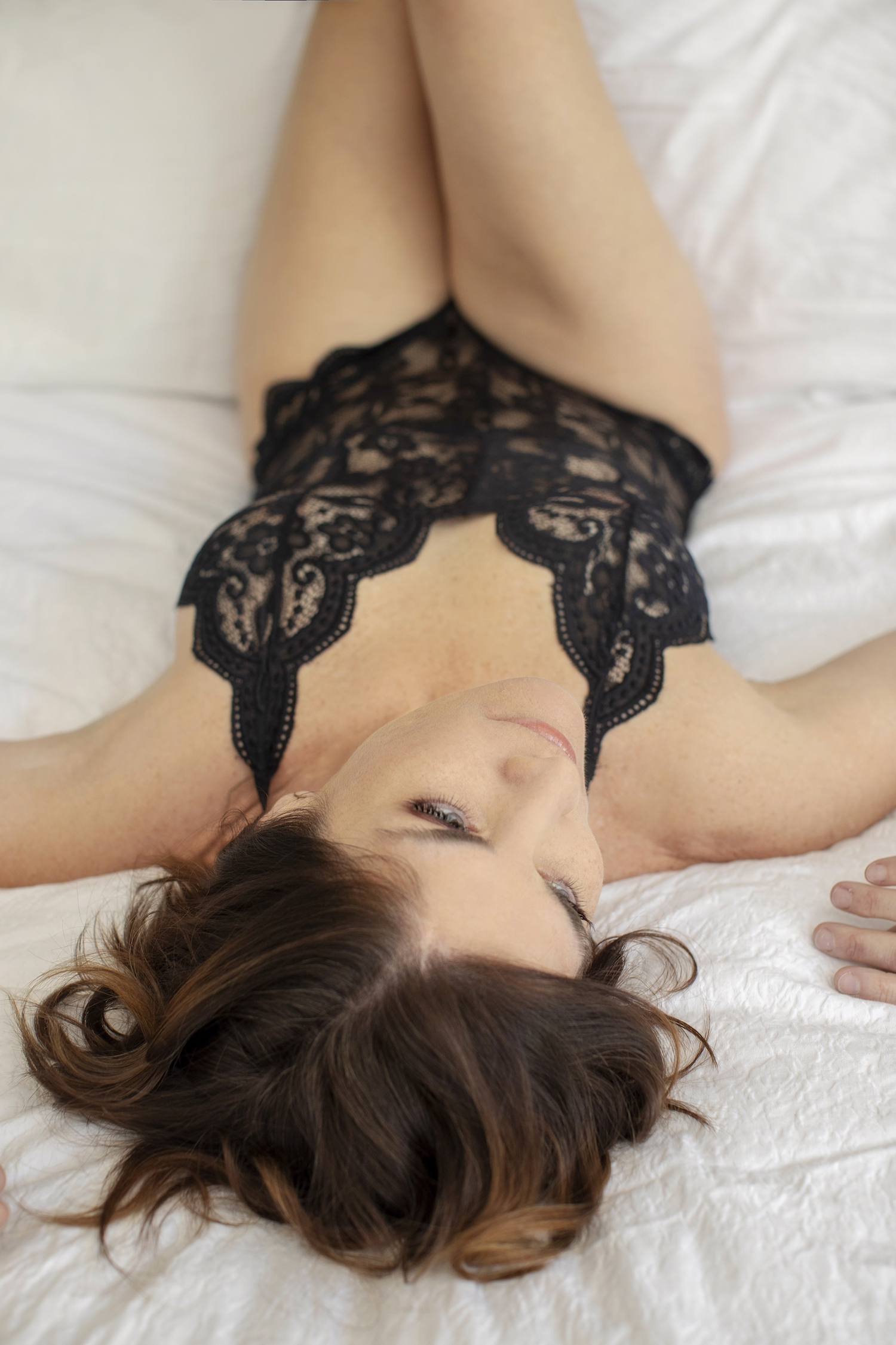 Boudoir style photograph of a woman lying on a bed with black lingerie.