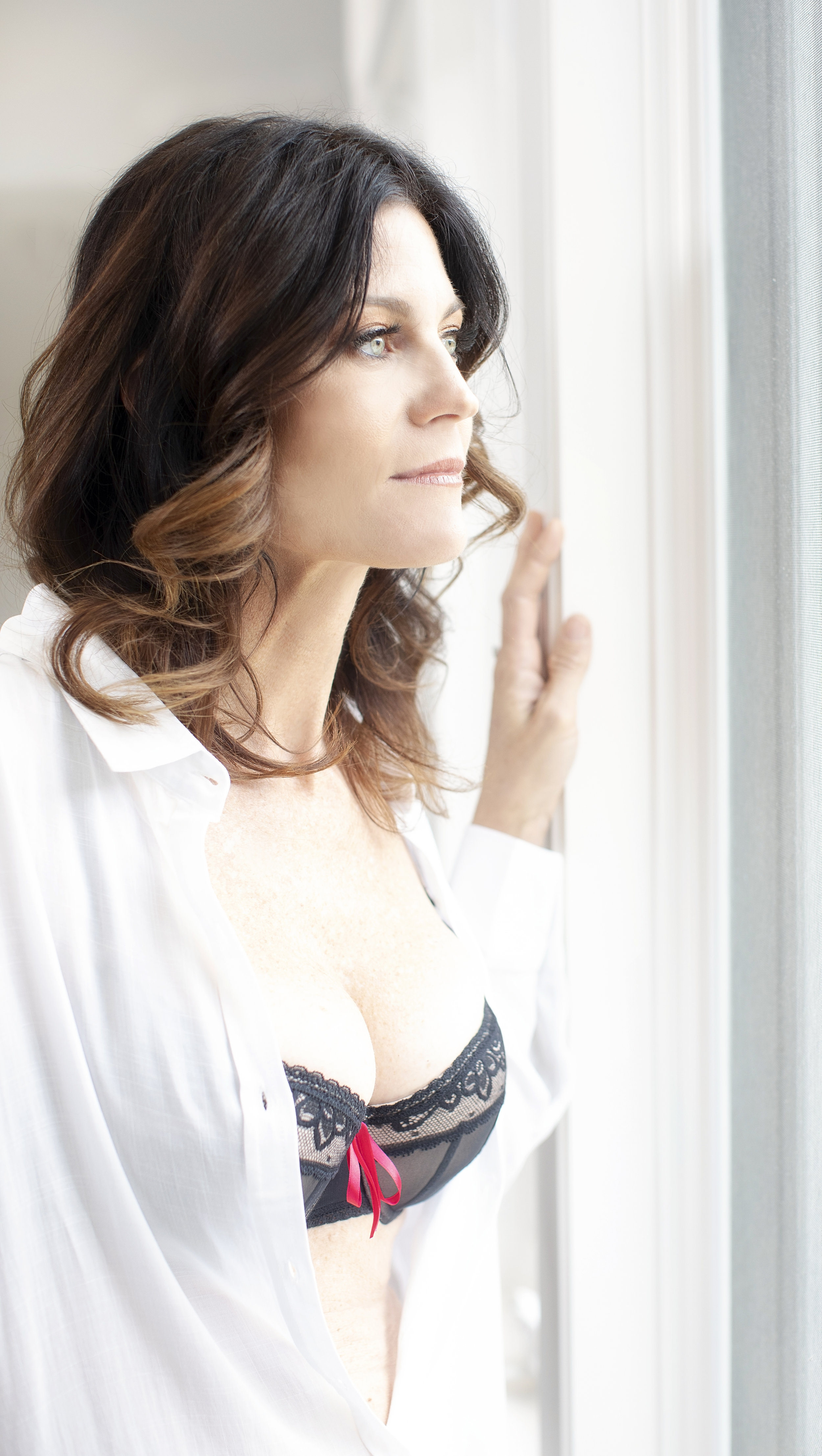 Boudoir session of a woman in black lingerie and a white shirt looking out of the window.