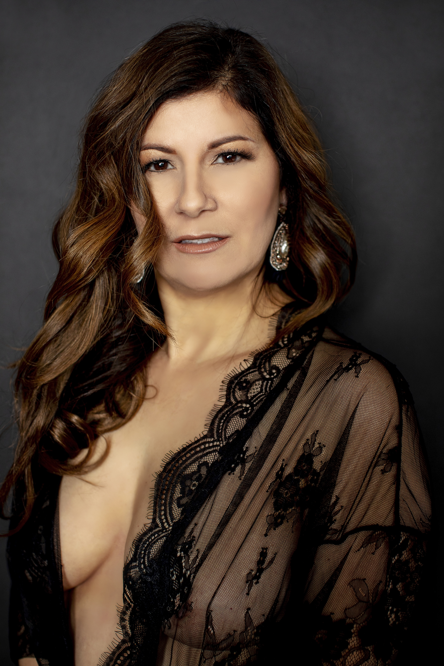 Boudoir photography of a woman in a black lace cover up.
