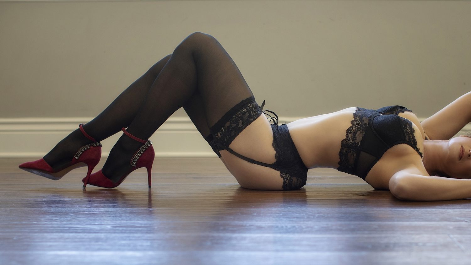 Sexy boudoir photo of a woman on a wooden floor with black lingerie and red heels.