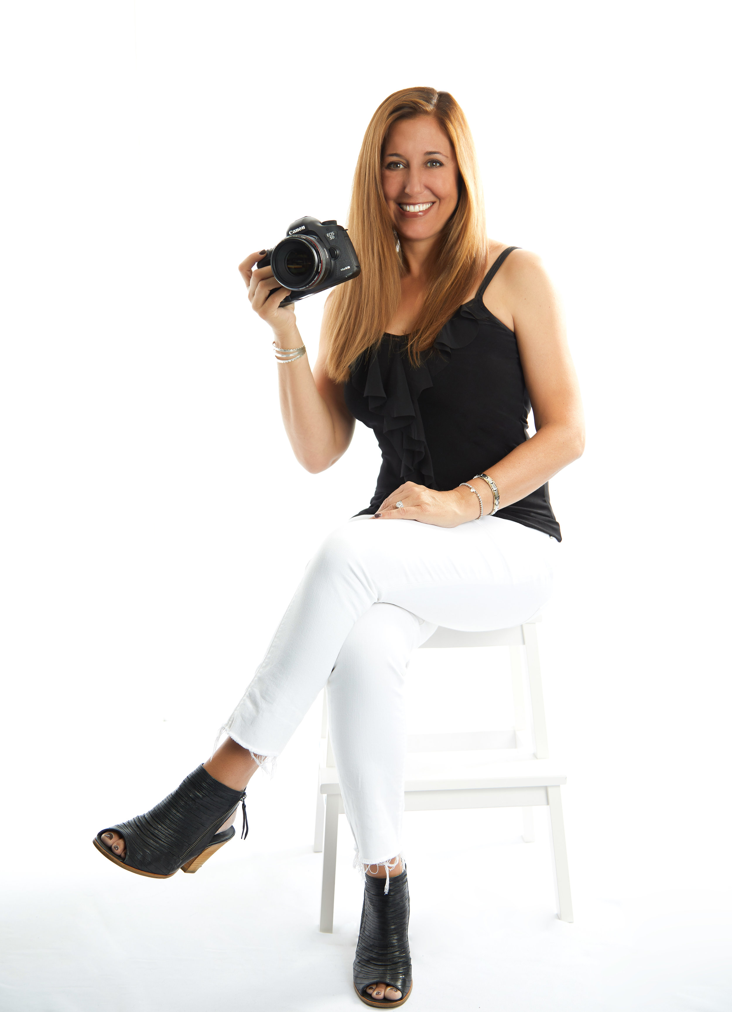 Missy Goldwyn, Boudoir Photographer in the San Francisco Bay Area, is wearing a black and white outfit while holding a camera.