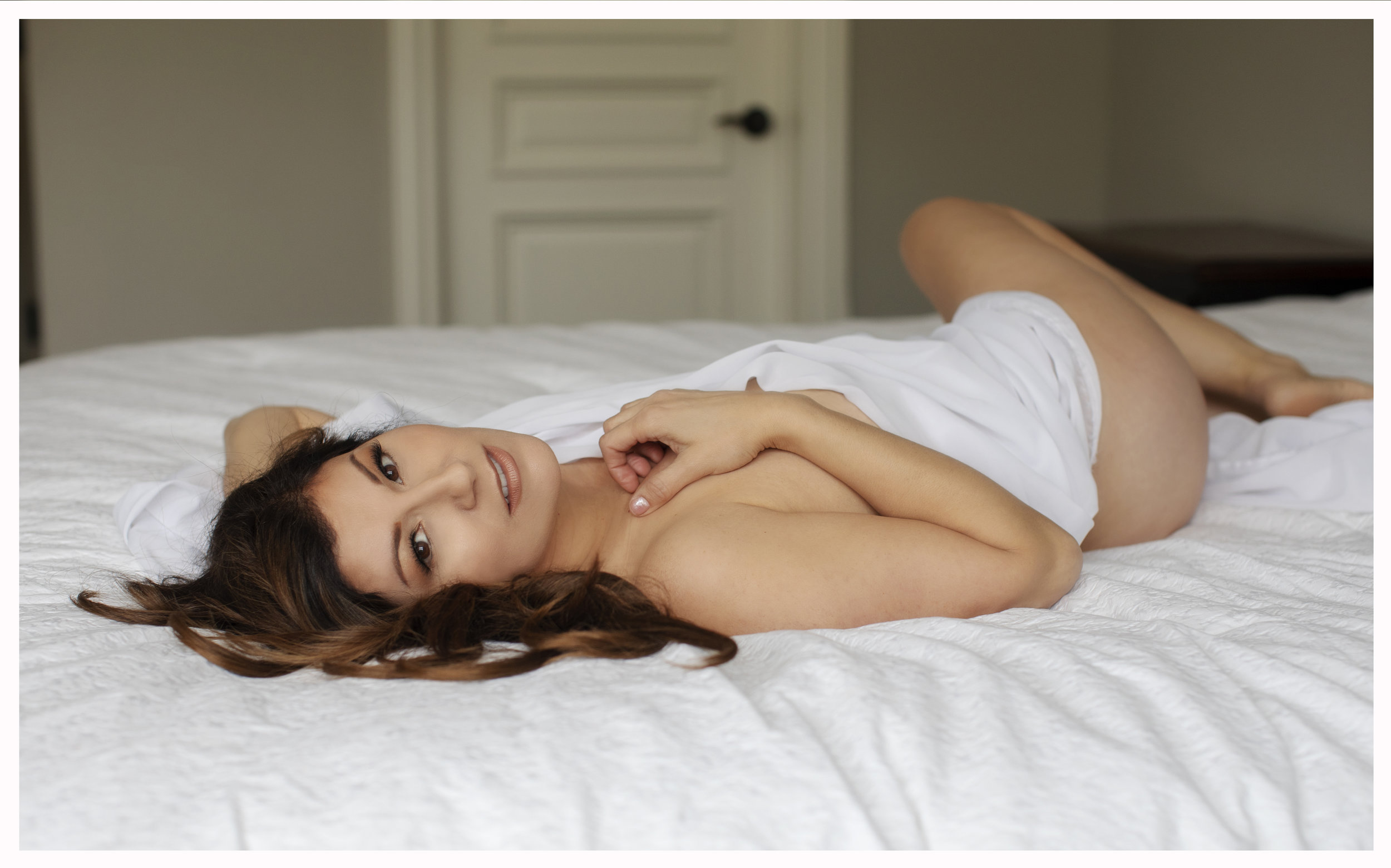 Boudoir photography of a woman on a bed draped in white bed sheets.