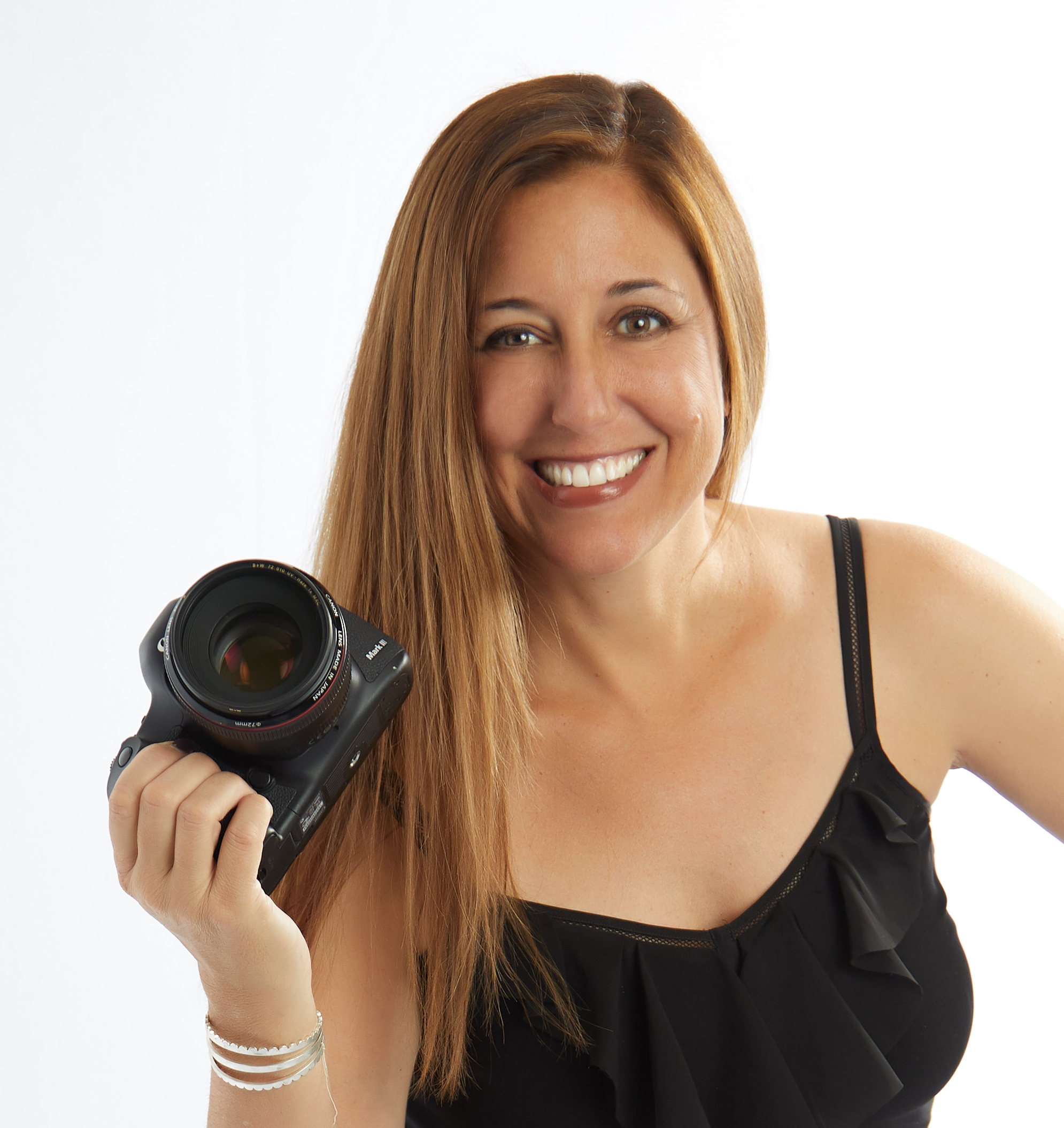 Missy Goldwyn, Boudoir Photographer in the San Francisco Bay Area, is smiling and holding a camera.