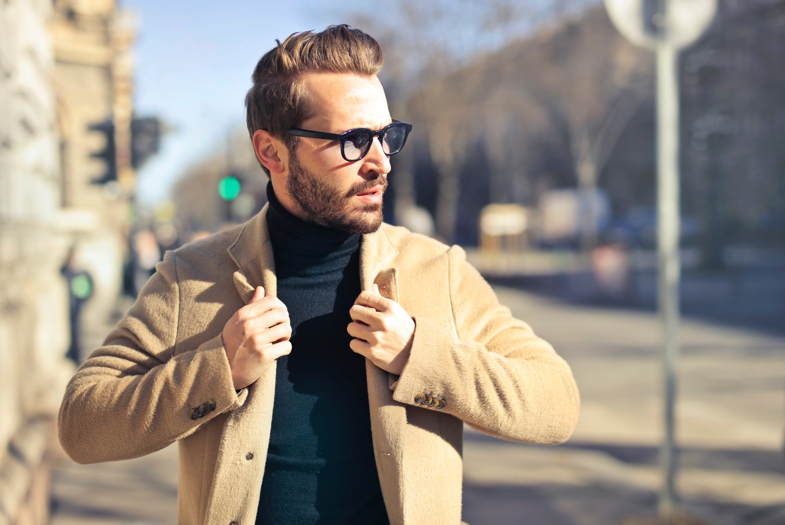 Man with glasses holding his coat. AND, SWIPE RIGHT client enjoyed his time working with AND, SWIPE RIGHT, Chloé Miller, and he likes his new dating profile.