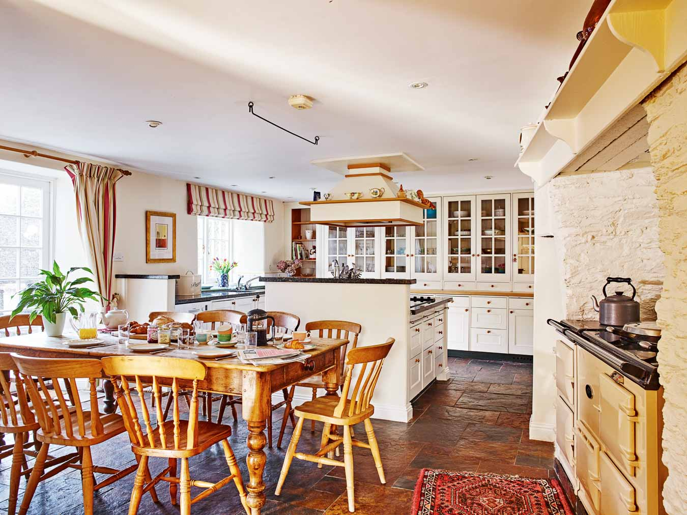 The large and homely country style kitchen with rustic table, Aga and generous built in cupboards in Flear House.