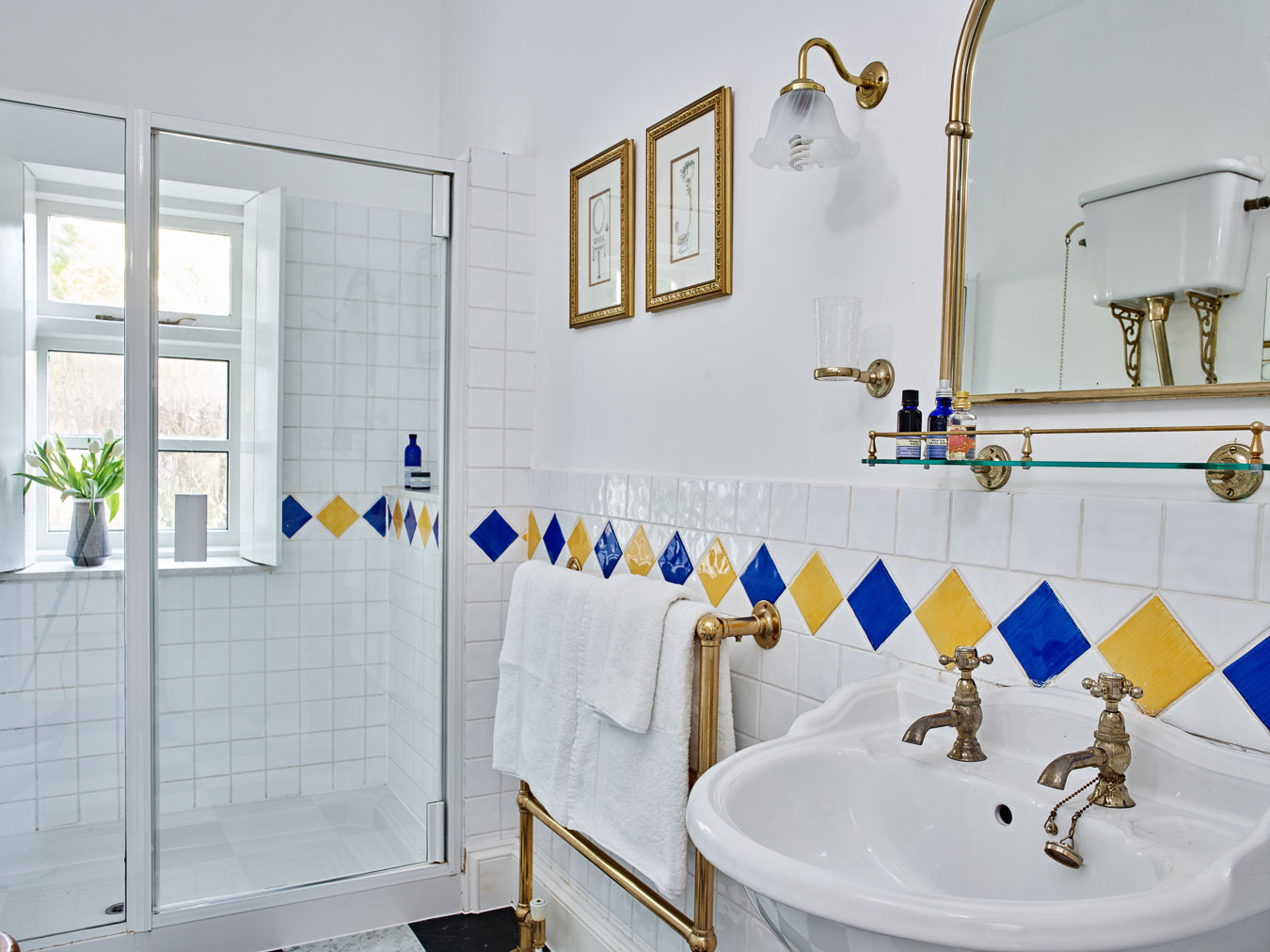 The near by bathroom that serves the twin rooms in Flear House. It has gold accessories and a fun Harlequin tile on the wall's and floor.
